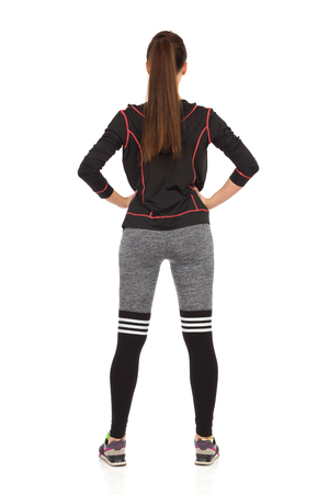 Rear view of young woman in fitness clothes holding hands on hip. Full length studio shot isolated on white.