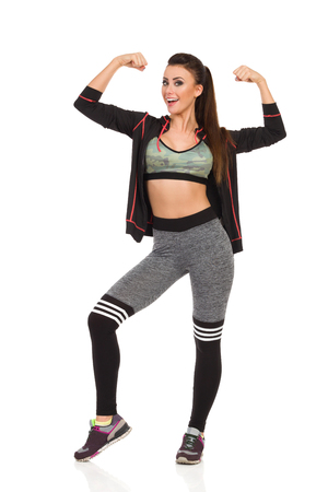 Happy beautiful young woman in fitness clothes is standing with arms raised, flexing muscles and talking. Full length studio shot isolated on white. Banco de Imagens