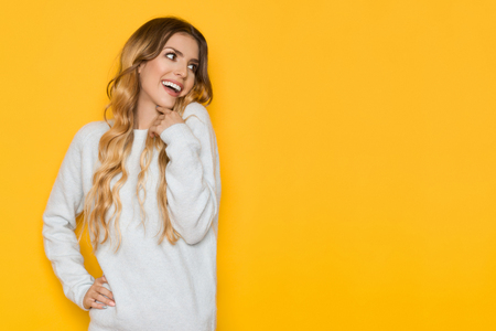 Beautiful young woman in light blue pastel sweater is holding hand on chin, smiling, and looking away. Waist up studio shot on yellow background.