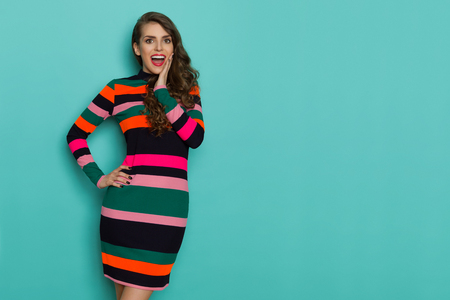 Excited beautiful young woman in colorful vibrant striped dress is posing with hand on chin, looking at camera and shouting. Three quarter length studio shot on turquoise background.