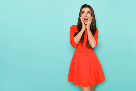 Beautiful young woman in red mini dress is holding head in hands, looking away and shouting. Three quarter length studio shot on turquoise background.