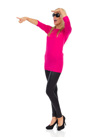 Beautiful blond woman in black leggings, high heels, pink sweater and sunglasses is standing, holding hand on forehead, looking away, pointing and shouting. Full length studio shot isolated on white. Stock Photo