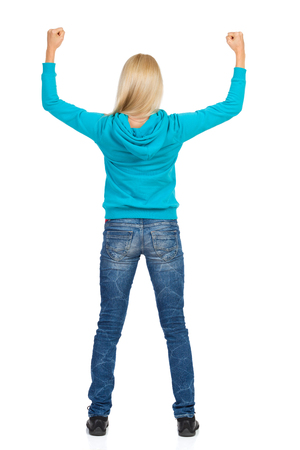 Blond young woman in turquoise hoodie and jeans is standing with arms raised and flexing muscles. Rear view. Full length studio shot isolated on white. Stock Photo