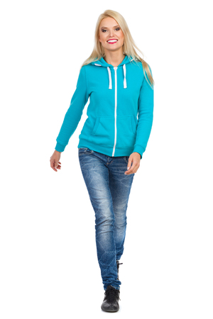 Smiling blond woman in turquoise hoodie and jeans is walking towards camera. Full length studio shot isolated on white.