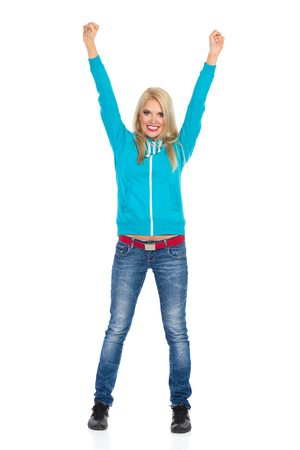 Smiling blond woman in turquoise hoodie and jeans is standing with arms raised, looking at camera and smiling. Full length studio shot isolated on white. Stock Photo