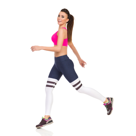 Young woman in sports clothes is jumping, looking at camera and smiling. Side view. Full length studio shot isolated on white. Stock Photo