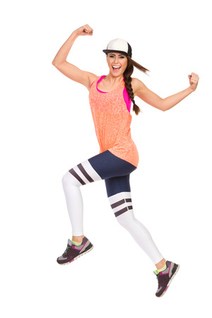 Young woman in sports clothes and baseball cap is jumping, looking at camera and laughing. Side view. Full length studio shot isolated on white. Stock Photo