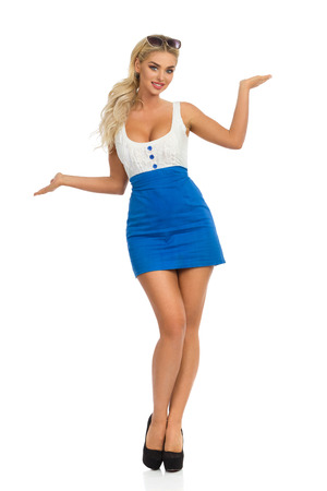 Beautiful blond woman in mini dress with neckline and high heels is standing with hands raised and comparing something. Full length studio shot isolated on white.