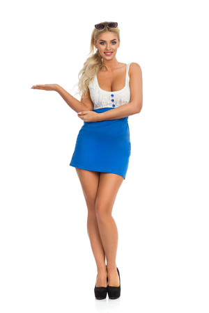 Beautiful sexy blond woman in mini dress with neckline and high heels is standing with hand raised and showing something. Full length studio shot isolated on white.