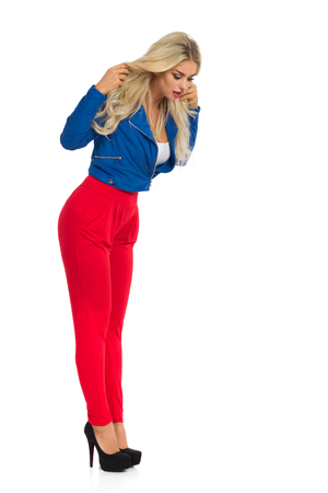 Surprised blond woman in red pants, blue jacket and high heels is standing and looking down. Full length studio shot isolated on white.
