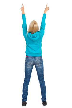 Blond young woman in turquoise hoodie and jeans is standing with arms raised and pointing up. Full length studio shot isolated on white.