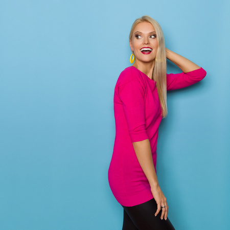 Happy beautiful blond woman in pink sweater is looking away over the shoulder and talking. Three quarter length studio shot on turquoise background.