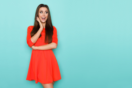 Beautiful young woman in red mini dress is holding hand on chin, looking away and shouting. Three quarter length studio shot on turquoise background.