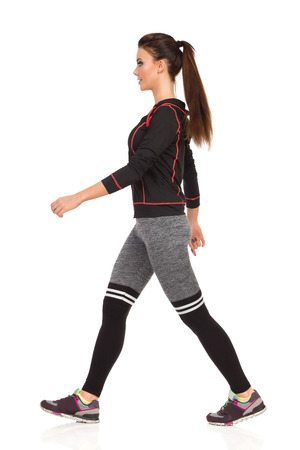 Young woman in sports clothes and leggings is walking, smiling and looking away. Side view. Full length studio shot isolated on white. Stock Photo