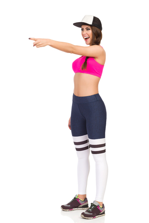 Young woman in pink sports bra, leggings and cap is looking away, laughing and pointing. Full length studio shot isolated on white.