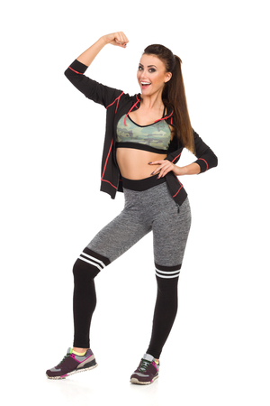 Laughing beautiful young woman in fitness clothes is standing with arms raised, flexing muscle and looking at camera. Full length studio shot isolated on white. Banco de Imagens