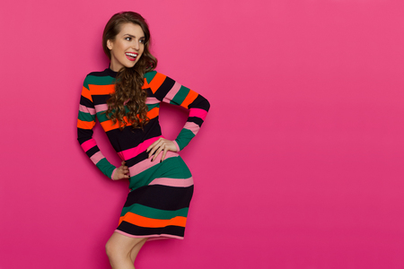 Beautiful young woman in colorful vibrant striped mini dress is looking over the shoulder and laughing. Three quarter length studio shot on pink background.