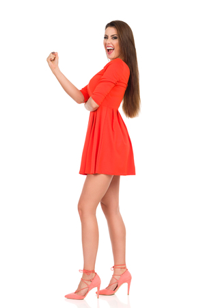 Beautiful young woman in red mini dress and high heels is standing, shouting, looking at camera and clenching fist. Side view. Full length studio shot Isolated on white.