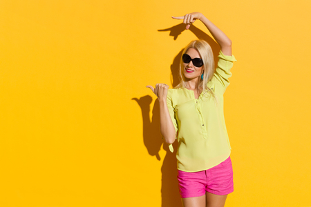 Beautiful blond woman in yellow shirt and pink shorts is standing with arms raised, looking away and pointing. Three quarter length studio shot on yellow background.