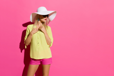 Beautiful blond woman in yellow shirt pink shorts and white sun hat is standing in sunlight and looking away. Three quarter length studio shot on pink background. Stock Photo