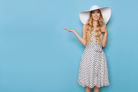 Beautiful young woman in white dotted summer dress and sun hat is standing, presenting, smiling and showing thumb up. Three quarter length studio shot on turquoise background.