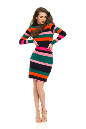 Beautiful young woman in colorful striped mini dress and high heels is holding hands on hip and looking away. Full length studio shot isolated on white. Stock Photo