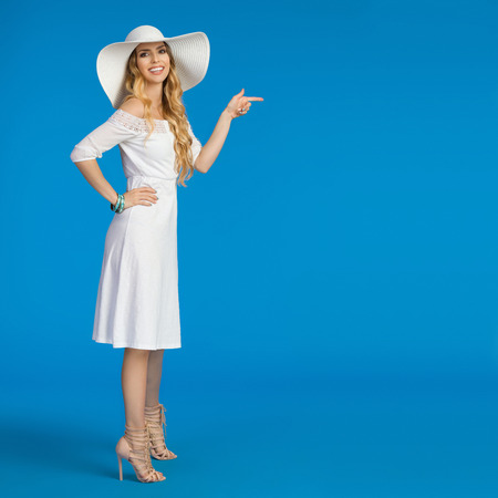 Beautiful young woman in white summer dress, high heels and sun hat is standing, pointing and looking at camera, Side view. Full length studio shot on blue background.