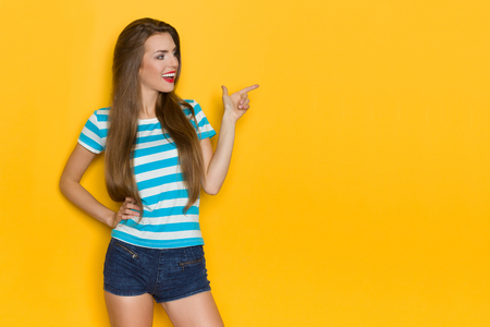 Beautiful young woman in striped t-shirt and jans shorts is looking away, pointing and talking. Three quarter length studio shot on yellow background.
