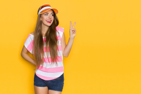 Smiling attractive young woman in pink striped shirt is showing victory hand sign and looking away. Three quarter length studio shot on yellow background.