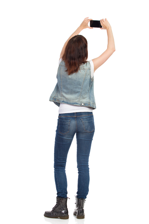 Rear view of young woman in jeans vest and black boots is standing, holding cell phone over her head and taking photo. Full length studio shot isolated. Stock Photo