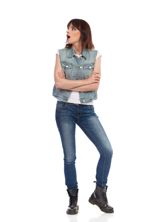 Shocked young woman in jeans vest and black boots is standing with arms crossed and looking away. Full length studio shot isolated on white.