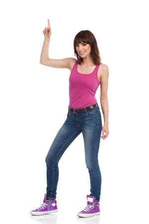 Smiling young woman in magenta tank top, jeans and sneakers is standing, pointing up and looking at camera. Full length studio shot isolated on white.