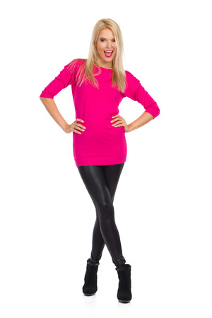 Beautiful blond woman in black leggings, high heels and pink sweater is standing with legs crosses, talking and winking. Front view. Full length studio shot isolated on white.