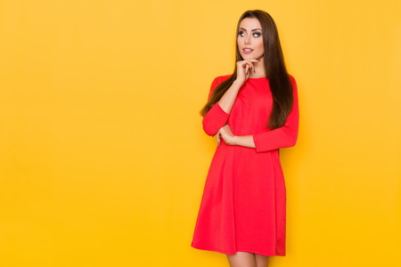 Beautiful young woman in red mini dress is holding hand on chin and looking away. Three quarter length studio shot on yellow background.