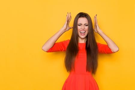 Boos jonge vrouw in rode mini-jurk houdt hoofd in handen en schreeuwt. Drie kwart lengtestudio die op gele achtergrond is ontsproten.