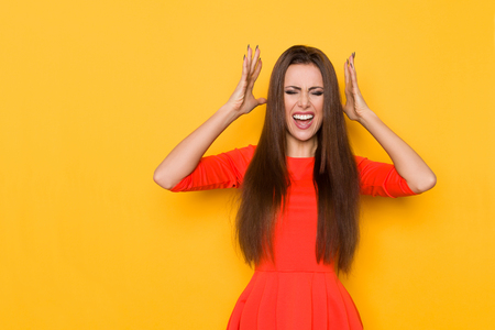 Upset young woman in red mini dress is holding head in hands and shouting. Three quarter length studio shot on yellow background.