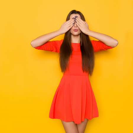 Beautiful young woman in red mini dress holds hands on her face and covers her eyes. Three quarter length studio shot on yellow background.