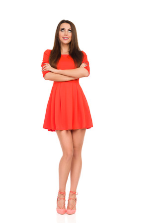 Fashion model in red mini dress and high heels is standing, holding arms crossed, smiling and looking up. Full length studio shot Isolated on white.