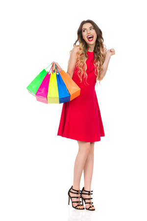 Happy beautiful young woman in red dress and high heels is standing, holding colorful shopping bags, shouting and looking away. Full length studio shot isolated on white.