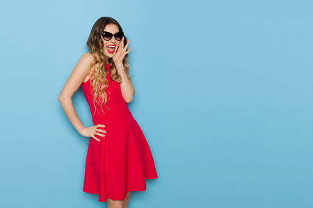 Beautiful young woman in red mini dress and sunglasses is holding hand on chin, looking at camera and shouting. Three quarter length studio shot on blue background.