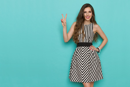 Smiling beautiful woman in black and white striped dress showing thumb up and looking at camera. Three quarter length studio shot on turquoise background.