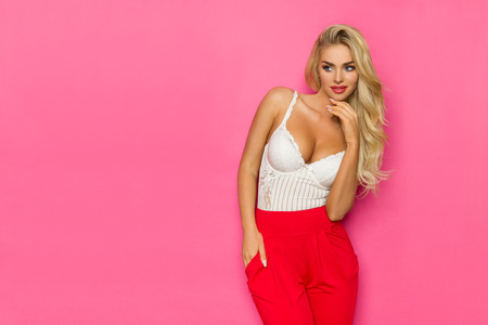 Beautiful blond woman in white corset and red trousers is holding hand on chin and looking away at copy space. Three quarter length studio shot on pink background.