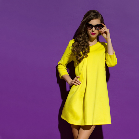 Beautiful young woman in yellow mini dress and sunglasses. Three quarter length studio shot on purple background.
