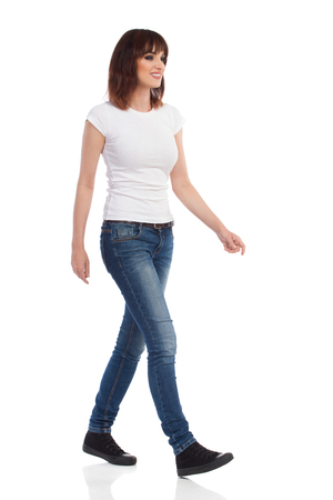 Young woman in white t-shirt, jeans and sneakers is walking and looking away. Front side view. Full length studio shot isolated on white.