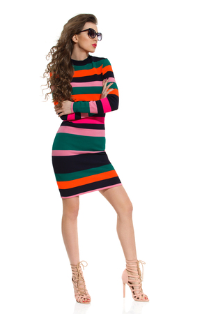 Beautiful young woman in colorful striped mini dress, sunglasses and high heels is standig with arms crossed and looking away. Full length studio shot isolated on white. Stock Photo