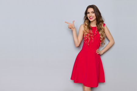 Beautiful young woman in red dress is pointing at gray copy space and smiling. Three quarter length studio shot on gray background.