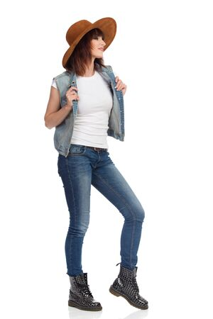 Beautiful young woman in brown suede hat is standing holding unbuttoned jeans vest, showing white t-shirt and looking away. Full length studio shot isolated on white.