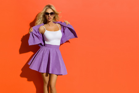 Blond beautiful woman in sunglasses and mini skirt is holding her unbuttoned jacket and looking at camera. Three quarter length studio shot on orange background. Imagens