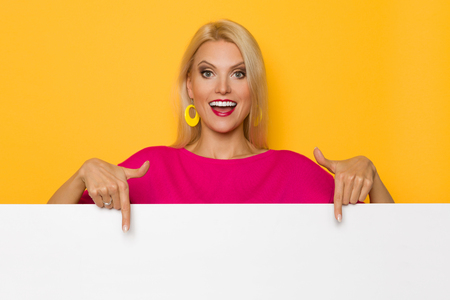 Beautiful blond woman in pink sweater is standing behind white banner, pointing at it and talking. Studio portrait on yellow background.