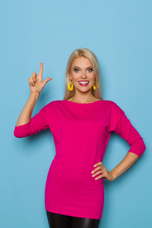 Beautiful blond woman in pink sweater is looking at camera, pointing up and smiling. Three quarter length studio shot on turquoise background.